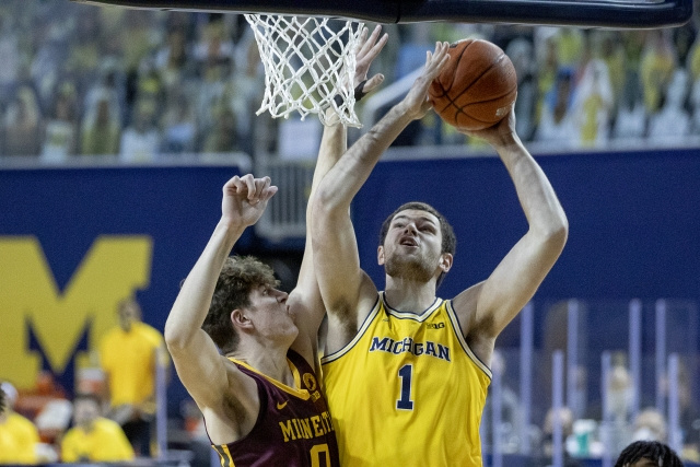 Michigan Center Hunter Dickinson (1) Gets By the Minnesota Defender for a Basket.