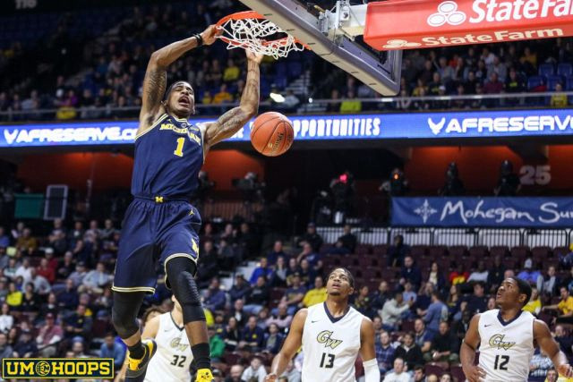 Michigan Guard Charles Matthews (1) Gets by the George Washington Defenders for a Dunk.