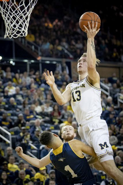 Michigan Forward Ignas Brazdeikis (13) Goes to the Basket Over the Chattanooga Defender.