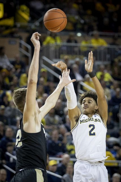 Michigan Guard Jordan Poole (2) Shoots and Makes a Three Pointer Over the Purdue Defender.