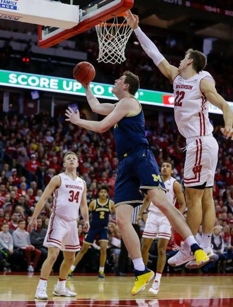 Michigan Forward Jon Teske (15) Gets by the Wisconsin Defender for a Basket.