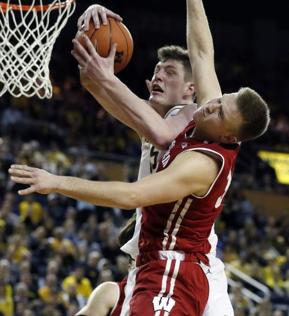 Michigan Center Jon Teske (15) Muscles by the Wisconsin Defender for a Basket.