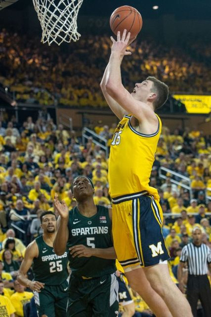 Michigan Center Jon Teske (15) Gets by 2 Michigan State Defenders for a Basket.