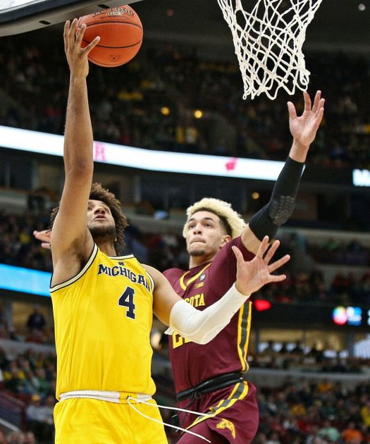 Michigan Forward Isaiah Livers (4) Gets by the Minnesota Defender for a Lay-up.