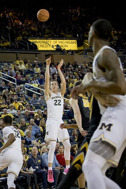 Michigan Guard Duncan Robinson (22) Shoots and Makes a Three Pointer.