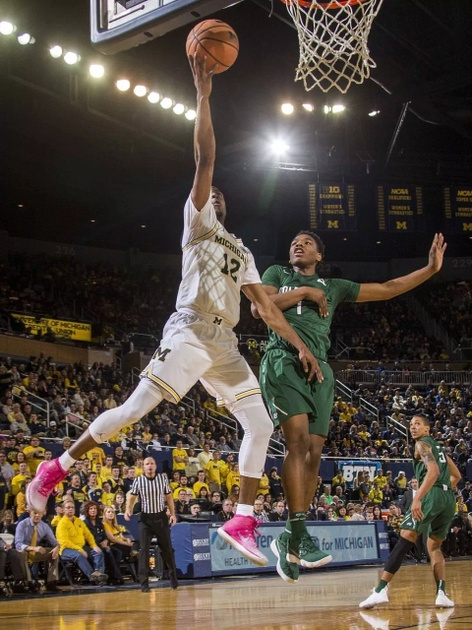 Michigan Guard Muhammad-Ali Abdur-Rahkman (12) Gets Past the Jacksonville Defender for a Lay-up.