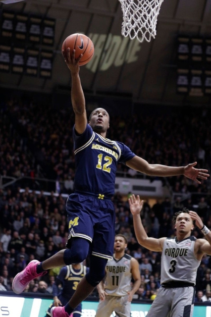 Michigan Guard Muhammad-Ali Abdur-Rahkman (12) Gets Past the Purdue Defender for a Lay-up.
