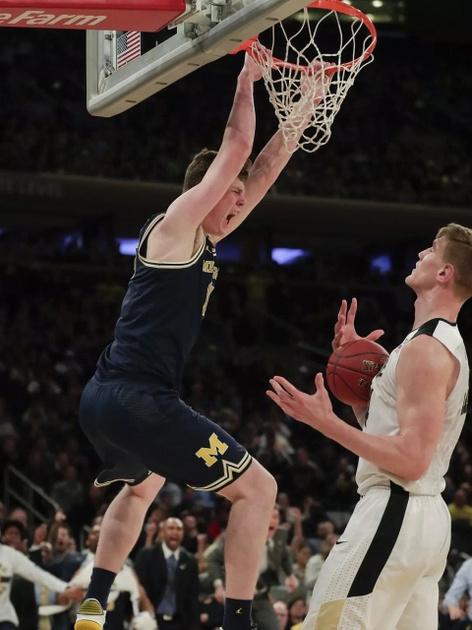 Michigan Center Jon Teske (15) Dunks the Ball Over the Purdue Defender.