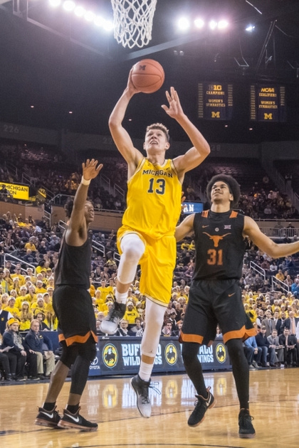 Michigan Forward Moritz Wagner (13) Goes to the Basket Between Two Texas Defenders.