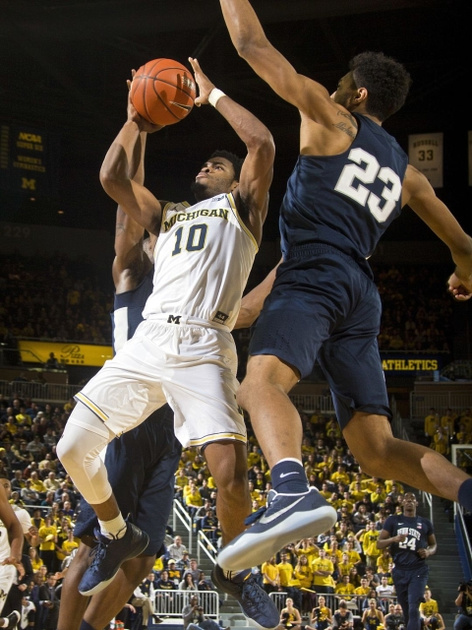 Michigan Guard Derrick Walton Jr. (10) Goes to the Basket Between 2 Penn State Defenders.