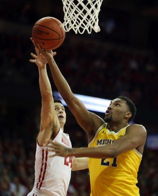 Michigan Guard Zak Irvin (21) Gets Past the Wisconsin Defender for a Basket.