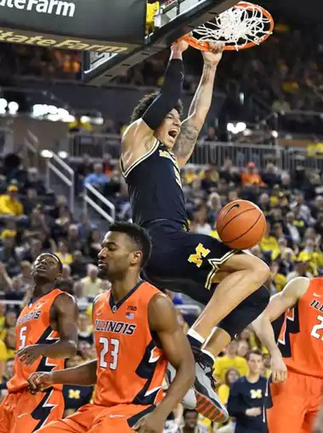 Michigan Forward D.J. Wilson (5) Dunks the Ball Over the Illinois Defenders.